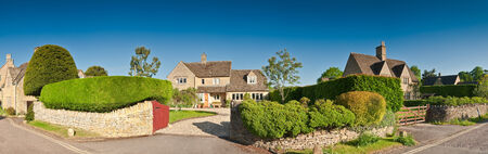 Welcoming family homes with well manicured hedges, gardens and pretty drystone walls, clear blue sky and warm early morning sunlight. Stitched panoramic image.