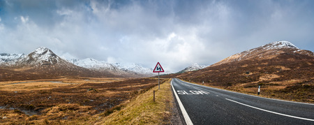 Open road leading through the dramatic Scottish Highlands of Glen Coe, Scotland