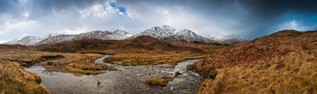 snowcapped: Scottish Highlands of Glen Coe, snowcapped mountains,meandering river and dramatic storm broken sky