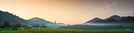 amanecer: Amanecer que se rompe sobre las montañas brumosas villas rústicas y tierras de cultivo tradicional en Italia.