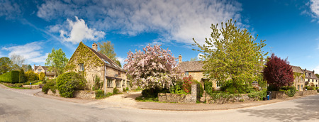 Traditional rural homes, immaculate gardens and pretty spring blossom tree create an idyllic village scene.