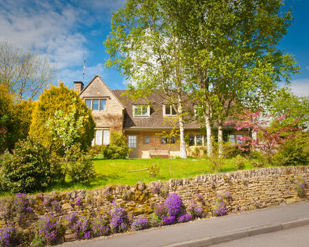 detached houses: Traditional rural homes, immaculate gardens and pretty spring blossom tree create an idyllic village scene  Editorial