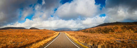 natural  moody: Open road leading through the Scottish Highlands of Glen Coe, snowcapped mountains and dramatic storm broken sky. Stock Photo
