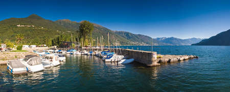 Morning sun illuminating peaceful harbor on Lake Maggiore. photo
