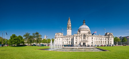 Magnificent City Hall in the heart of the Cardiff, Welsh and European flags visible. Perspective corrected stitched panorama detailed when viewed large. Stock Photo
