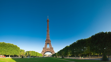 Iconic Eiffel Tower (1889) symbol of Paris and Champ-De-Mars park with clear blue sky, still the tallest building in town standing at a mighty 1063 ft. Stock Photo