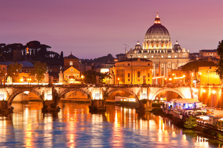 Highly detailed panoramic of the stunning renaissance church, St Peters Basilica (1692) reflected in the river Tiber by pretty night time illuminations, Vatican City Rome.