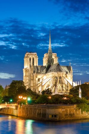 convent: Pretty evening illuminations of the stunning Notre-Dame Cathedral (1163) and parisian apartments along the banks of the river Siene, Paris.