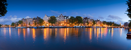 Pretty starry night time illuminations of dutch doll houses reflected in the tranquil canals of Amsterdam. photo