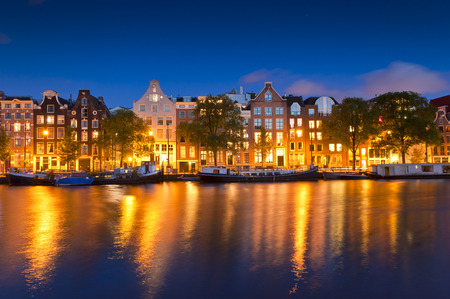 Pretty starry night time illuminations of dutch doll houses reflected in the tranquil canals of Amsterdam.