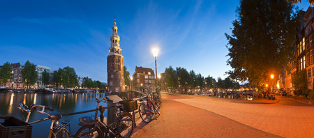 ubiquitous: Pretty night time illuminations of the Montlebaanstoren Tower (1512) overlooking Oosterdok and the ubiquitous dutch bicycles in central Amsterdam. Stock Photo