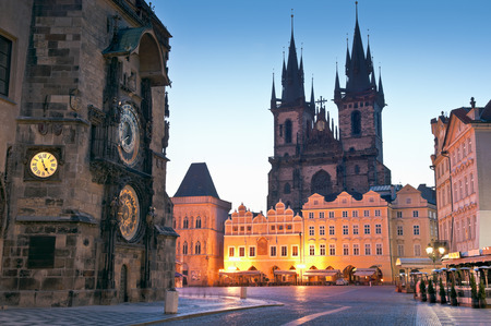 old town square: Night time illuminations of the the Old Town Hall (15th Century), Town Square and fairy tale Church of our Lady Tyn (1365) in the Magical city of Prague. Astronomical clock visible. Stock Photo