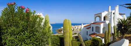 伝統的なヴィラと穏やかな青い海を見下ろす穏やかな風光明媚な景色。 写真素材