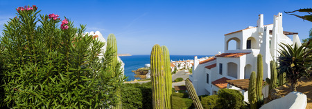spanish architecture: Serene scenic view over looking traditional villas and calm blue sea. Stock Photo