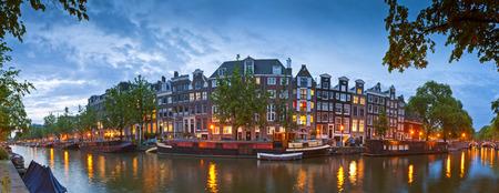네덜란드어 인형 집의 예쁜 야간 조명은 암스테르담의 조용한 운하에 반영.