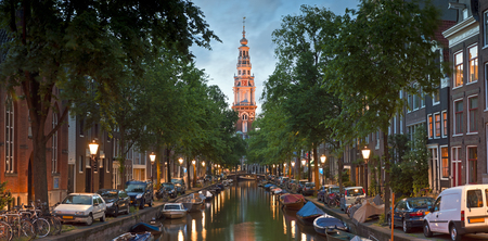 Pretty night reflections and illuminated church spire in the tranquil canals of Amsterdam, Holland.