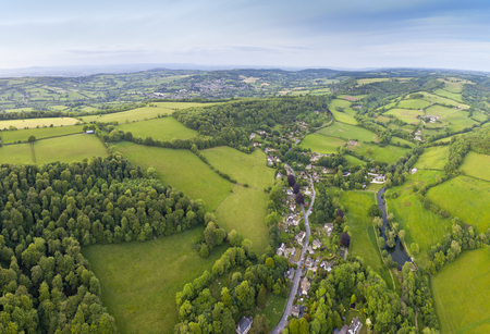 gloucestershire: Dramatic aerial view of idyllic rolling patchwork farmland with pretty wooded boundaries, lit in warm early evening sunshine in the heart of the Cotswolds, England