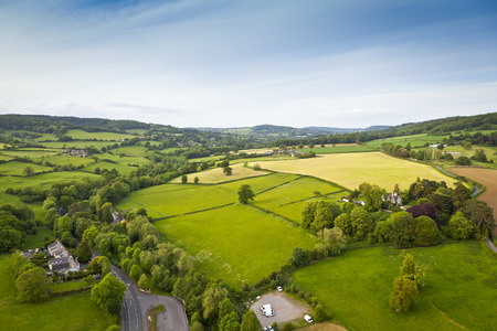 Dramatic aerial view of idyllic rolling patchwork farmland with pretty wooded boundaries, lit in warm early evening sunshine in the heart of the Cotswolds, England