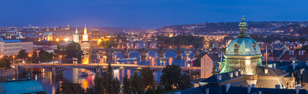 prague: Pretty night time glow of the magical city of Prague reflected in the Vltava river, many sights visble including Charles bridge, Strakova Akademie and Church of Our Lady Tyn. Stock Photo