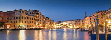 Pretty night time illuminations of the iconic Rialto Bridge (1591) and Venetian Villas over the grand canal in Venice