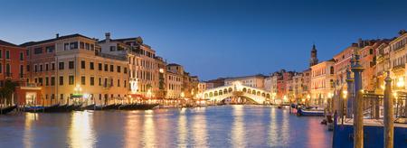 Pretty night time illuminations of the iconic Rialto Bridge (1591) and Venetian Villas over the grand canal in Venice