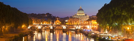 St Peters Basilica (1692) reflected in the river Tiber by pretty night time illuminations, Vatican City Rome.