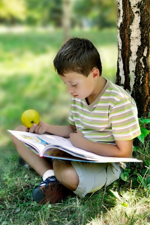 A boy with apple reads book at the tree  photo