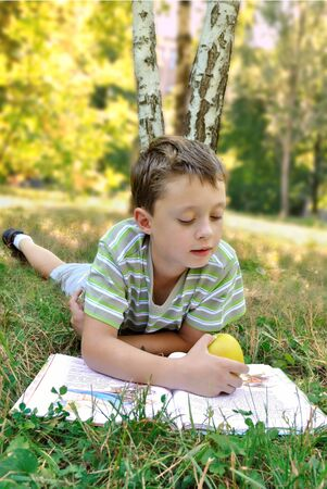 A boy with apple reads book on the grass photo