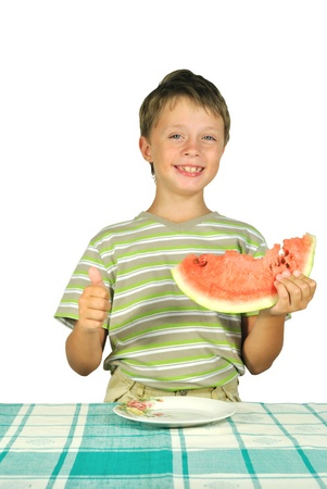 The boy with melon at the table Stock Photo - 10563484