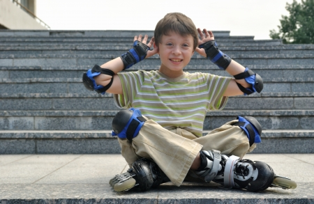 susceptibility: The jolly boy with roller blades sitting at the granite pavement