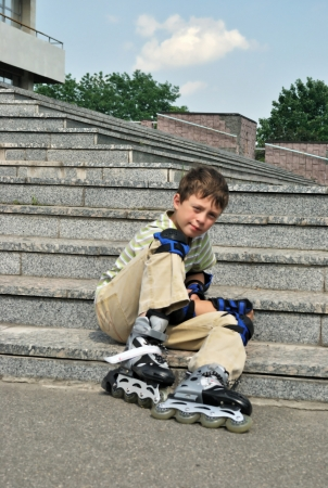susceptibility: The tired boy with roller blades rests at the steps