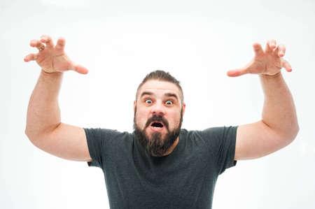 Wütender Typ in den grauen Hemd , die Hände anhebt und versucht , jemand über weißem Hintergrund zu erschrecken Standard-Bild - 99327526