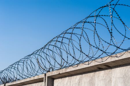 Barbwire in prison or other guarded object with blue sky background.
