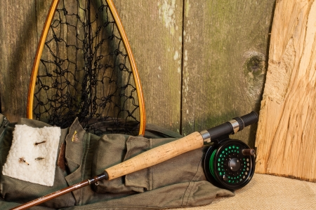 Fly fishing gear on burlap against ceader wood wall Stock Photo