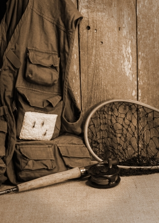 Fly fishing gear on burlap against ceader wood wall Stockfoto