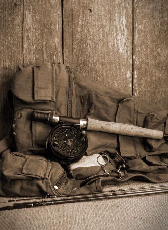 fishing pole: Fly fishing gear on burlap against ceader wood wall Stock Photo