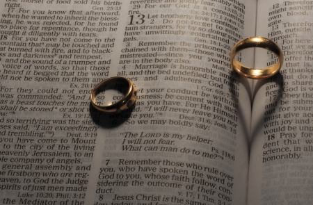 wedding rings making heart shaped shadows on bible pages photo