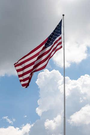 flag pole: American Flag flying on a flag pole