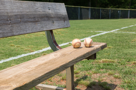 little league: Baseball on a bench in a little league field Stock Photo
