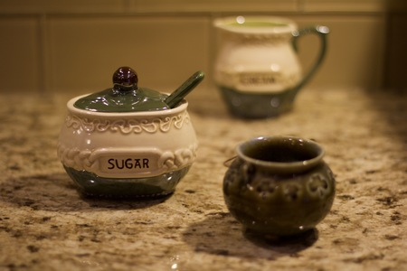 Interior shallow depth of field stock photo of irish sugar container in foreground with blurred irish creamer container and bowl in background on brown granite countertop with glass tile backsplash background Stock Photo