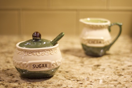 Interior shallow depth of field stock photo of irish sugar container in foreground with blurred irish creamer container in background on brown granite countertop with glass tile backsplash background