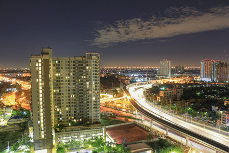 Apartment windows at night near the modern highway system with heavy traffic. The business district is far away from this residential district mostly full of high rise condos. Stock Photo