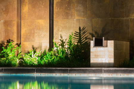 privileged: Peaceful pool reflections along jungle greenery planted near the pool, casting shadows upon a wall with great mood lighting in the evening.  Luxury high-end swimming pool, room for copyspace.