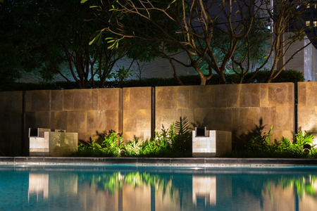 Romantische Abendstimmung Beleuchtung Schatten auf einer romantischen Umgebung in der Nähe des Pool zu werfen. Das luxuriöse Haus verfügt über einige der besten Gärten und tropische Flora der Welt.