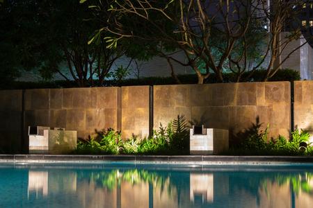 Romantyczne wieczorne oświetlenie nastrojowe rzuca cienie na romantyczną scenerię przy basenie. Ten luksusowy dom ma jedne z najlepszych ogrodów i tropikalnej flory na świecie.