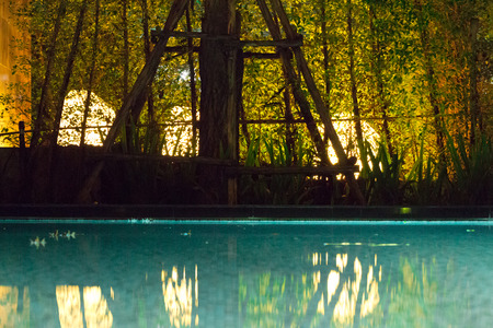 This eerie and unsettling scene reminds me of halloween with long shadows casting through the darkness and reflecting off the surface of the swimming pool.  Mood lighting.
