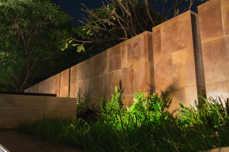 Soft shadows casting onto a landscaped wall with nice mood lighting in the evening near the swimming pool.  Nice design and layout with green grass and plants near lush trees.