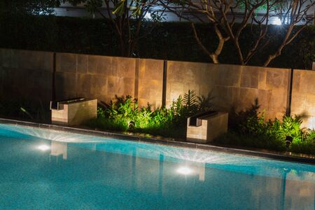 Reflets de piscine paisibles au milieu d'un éclairage d'ambiance et d'une végétation luxuriante donnant des ombres chaudes au travail de briques de designer. L'eau chaude au crépuscule est un endroit idéal pour nager dans un manoir de millionnaires.