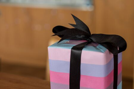 A christmas present with black bow and purple pink wrapping papper, neatly wrapped.  Soft glow of christmas lights in the blurred background.  Dusty ribbon.  Room for copysapce.