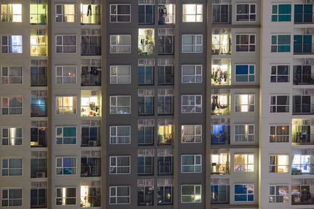 rentals: Apartment windows at night showing a new high rise condo with good real estate rentals and spaces to buy.  Individual people living separate lives.